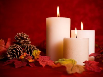 fall white lit candles with pine cones, leaves, and red background