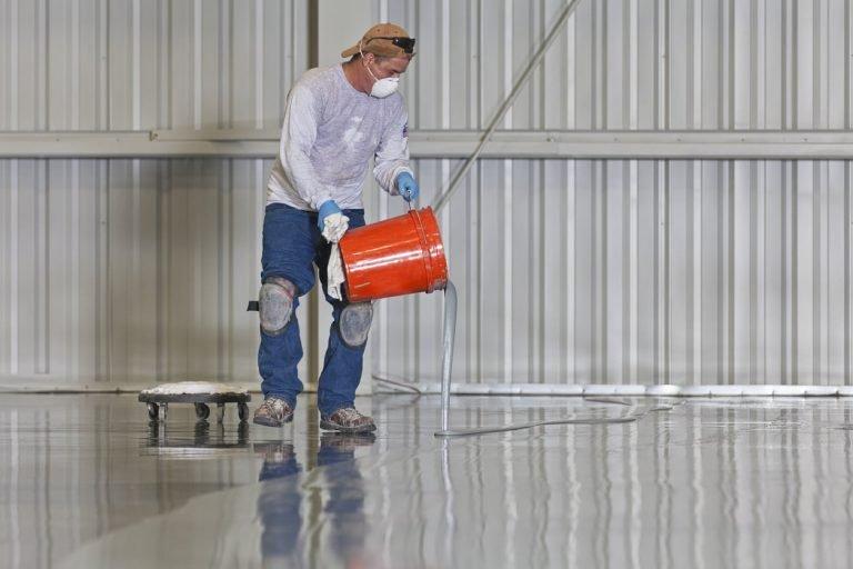 man applying epoxy on the floor
