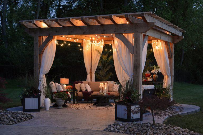 A concrete patio designed into a romantic gazebo surrounded with green landscape
